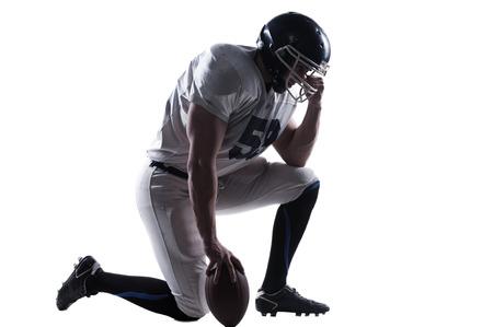 jugador de futbol americano: Vista lateral del jugador de f�tbol americano de la mano en el casco mientras est� de pie en la rodilla contra el fondo blanco