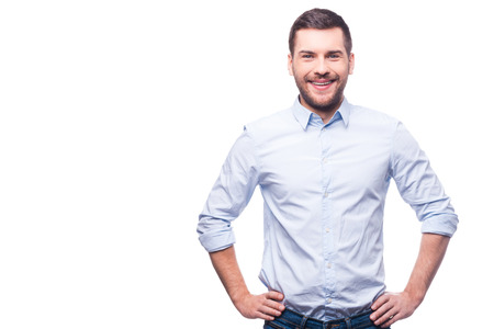 Handsome young man in shirt looking at camera and holding hands on hips while standing against white background