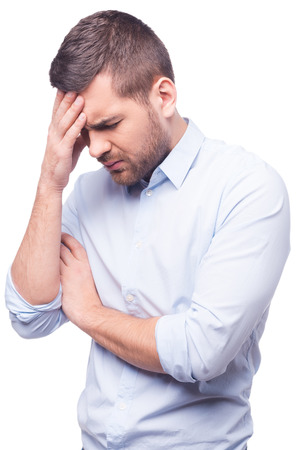 depressed person: Side view of young man in shirt touching his head and keeping eyes closed while standing against white background