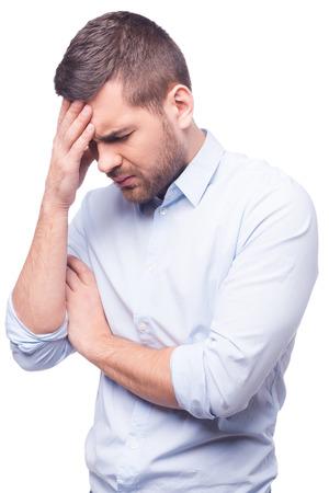 persona deprimida: Vista lateral del hombre joven en camisa tocando su cabeza y manteniendo los ojos cerrados mientras está de pie contra el fondo blanco Foto de archivo