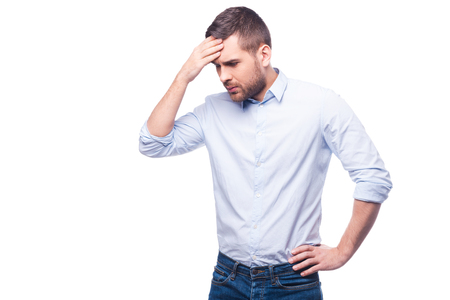 Frustrated young man in shirt touching head with hand while standing against white background photo