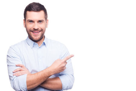 man: Businessman pointing copy space. Handsome young man in shirt looking at camera and pointing away while standing against white background