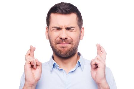 Portret van een jonge man in het shirt houden de vingers gekruist en de ogen gesloten tijdens het staan tegen een witte achtergrond