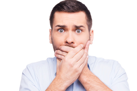 No way! Shocked young man in formalwear covering mouth with hands and looking at camera while standing against white background photo