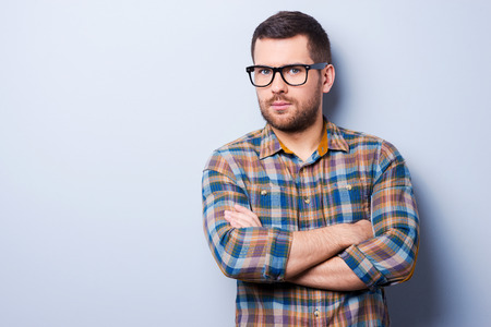 young adult men: Serious young man keeping arms crossed and looking at camera while standing against grey background