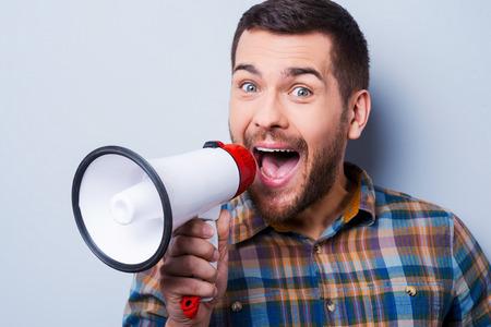 megafono: Apuesto joven gritando por un meg�fono mientras est� de pie contra el fondo gris. Foto de archivo