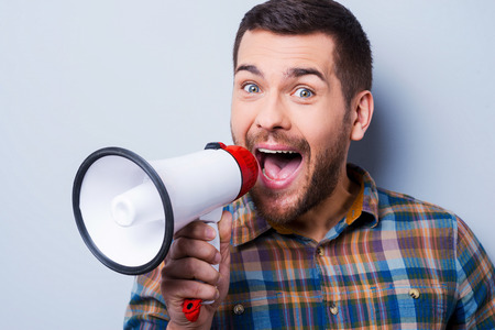 talking businessman: Handsome young man shouting through a megaphone while standing against grey background.