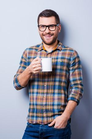 hombre tomando cafe: Joven caf� de consumici�n del hombre guapo y mirando a la c�mara mientras est� de pie contra el fondo gris