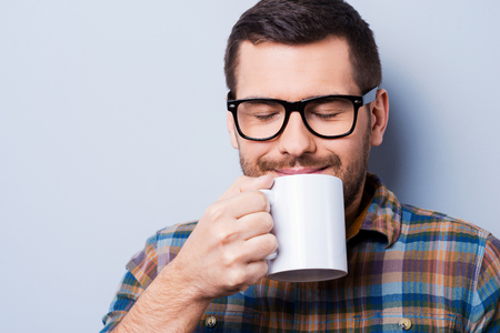 Handsome young man holding cup of coffee and keeping eyes closed while standing against grey background