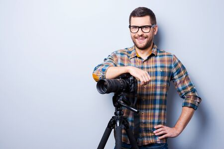 hand on hip: Portrait of confident young man in shirt holding hand on camera on tripod while standing against grey background Stock Photo