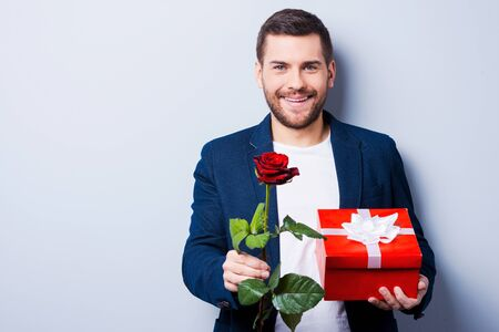 Handsome young man giving a gift and a flower to you while standing against grey background