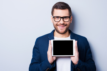 fun at work: Cheerful young man holding a digital tablet and smiling while standing against grey background Stock Photo