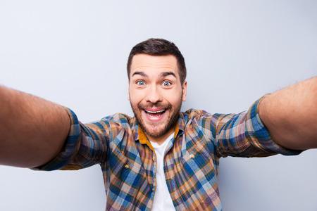 boca: Apuesto joven en camisa que sostiene la c�mara y haciendo Autofoto y sonriendo mientras est� de pie contra el fondo gris
