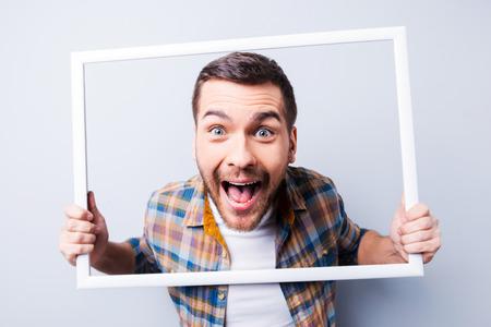 volto uomo: Giovane uomo in camicia in possesso di cornice di fronte al suo viso e sorridente mentre in piedi su sfondo grigio