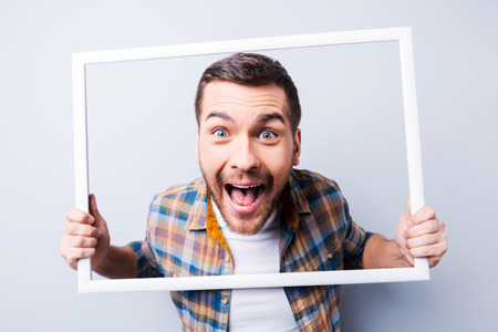 Handsome young man in shirt holding picture frame in front of his face and smiling while standing against grey background Stock Photo