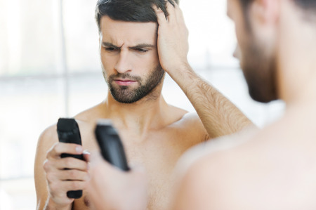 man holding a mirror. rear view of frustrated young man holding an electric shaver and looking at a mirror