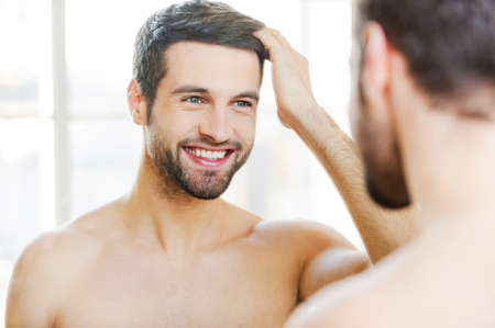 nude male body: Starting new day with smile. Handsome young man touching his hair with hand and smiling while standing in front of the mirror Stock Photo