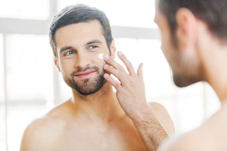 sex symbol: Skin care. Handsome young shirtless man applying cream at his face and looking at himself with smile while standing in front of the mirror