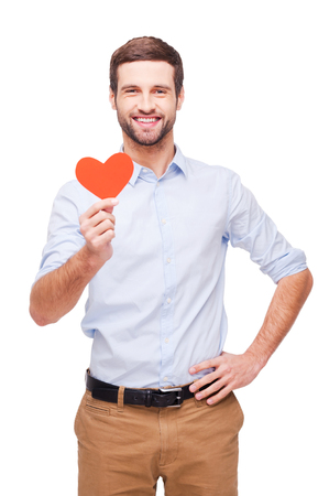 I give you my heart! Handsome young man holding heart shaped valentine card and smiling while standing isolated on white background photo