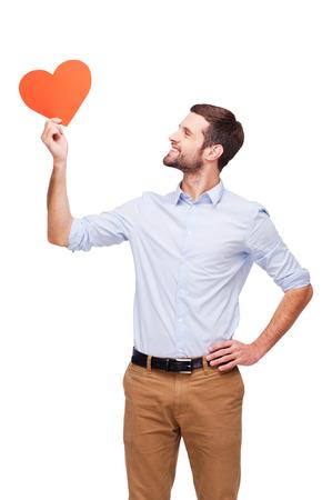 symbol hand: Liebe liegt in der Luft. H�bscher junger Mann mit herzf�rmige valentine Karte und Blick auf sie mit einem L�cheln, w�hrend stehend auf wei�em Hintergrund