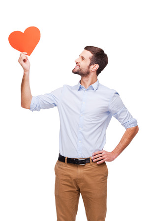 Love is in the air. Handsome young man holding heart shaped valentine card and looking at it with smile while standing isolated on white background photo
