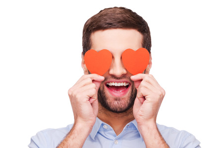 red eye: This is love! Handsome young man holding heart shaped valentine cards in front of his eyes and smiling while standing isolated on white background