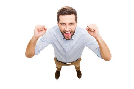 loteria: Ganador cotidiana. Vista superior de hombre joven feliz que expresa la positividad y gesticulando mientras que de pie aislado en fondo blanco