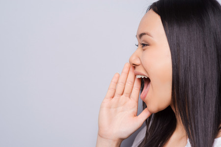 Sharing good news. Side view of beautiful young Asian woman shouting and holding hand near mouth while standing against grey background