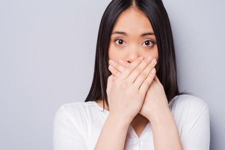 bouche: Oops! Surpris jeune femme asiatique se couvrir la bouche avec les mains et regardant la caméra tout en se tenant sur fond gris Banque d'images