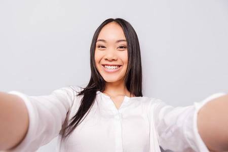 행복한 순간을 저장해야합니다. 카메라를 들고 회색 배경에 서있는 동안 selfie 만들기 쾌활한 젊은 아시아 여자