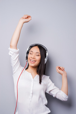 Happy music lover. Beautiful young Asian in headphones keeping eyes closed and arms raised while standing against grey background photo