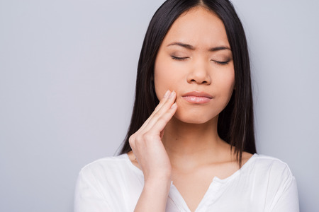 one young adult woman only: Toothache. Beautiful young Asian women touching her cheek and keeping eyes closed while standing against grey background