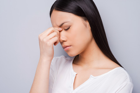 long depression: Depressed woman. Depressed young Asian woman touching her head with hands and keeping eyes closed while standing against grey background