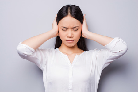 hands covering ears: Too loud sound. Beautiful young Asian women covering ears with hands and keeping eyes closed while standing against grey background Stock Photo