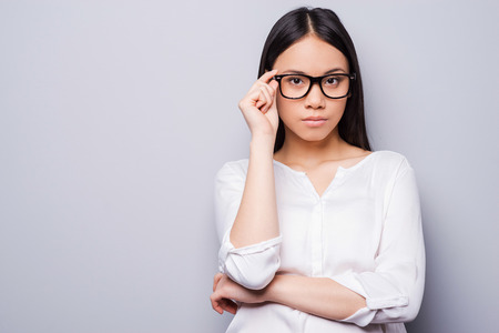 adjusting: Confident beauty. Beautiful young Asian woman in eyewear looking at camera and keeping arms crossed while standing against grey background