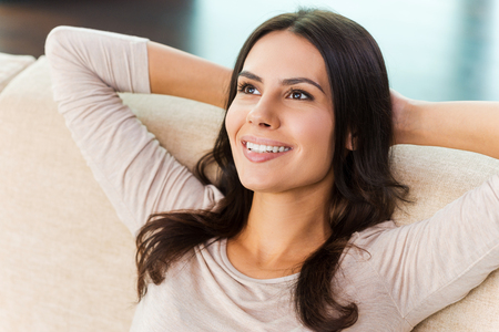 taking a break: Taking time to have a break. Top view of attractive young woman looking at camera and smiling while relaxing on the couch at home
