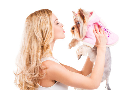 You are my friend! Side view of beautiful young blond hair woman carrying Yorkshire terrier in pink clothes and keeping eyes closed while standing isolated on white background photo