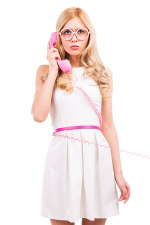 Blonde with telephone. Beautiful young blond hair woman talking on the pink telephone and smiling while standing isolated on white background photo