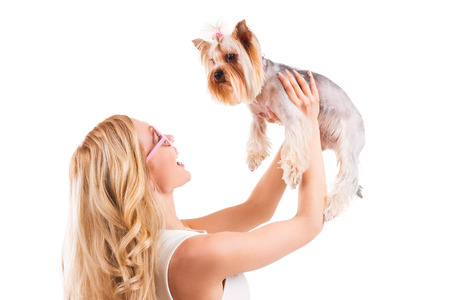 You are my best friend! Side view of beautiful young blond hair woman carrying Yorkshire terrier in pink clothes and smiling while standing isolated on white background photo