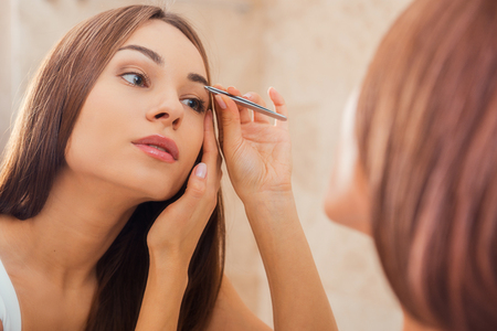sex symbol: Tweezing eyebrows. Beautiful young woman tweezing her eyebrows while looking at the mirror