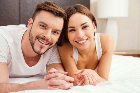 sexual nude: Loving couple in bed. Beautiful young loving couple lying in bed together and smiling Stock Photo
