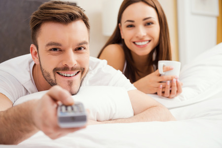 Loving couple in bed. Beautiful young loving couple lying in bed together and smiling while man holding remote control photo