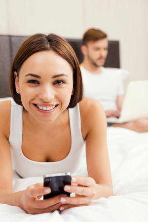 Enjoying their free time at home. Beautiful young woman holding mobile phone and smiling while lying in bed with man working on laptop in the background photo