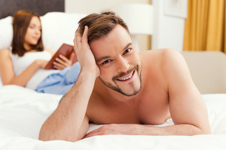 Feeling just happy. Handsome young and shirtless man lying in bed and smiling while woman reading a book in the background photo