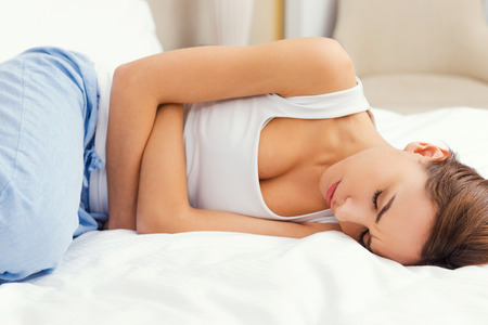 stomachache woman: Feeling awful stomachache. Frustrated young woman holding hands on stomach and keeping eyes closed while lying in bed