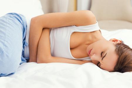 menstruacion: Sintiéndose horrible dolor de estómago. Frustrado joven de la mano en el estómago y manteniendo los ojos cerrados mientras está acostado en la cama Foto de archivo