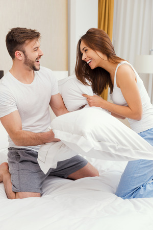 nude wife: Pillow fight. Beautiful young couple fighting with pillows in bed and smiling