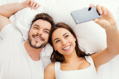 nude wife: Capturing happy moments. Top view of beautiful young loving couple lying in bed and making selfie