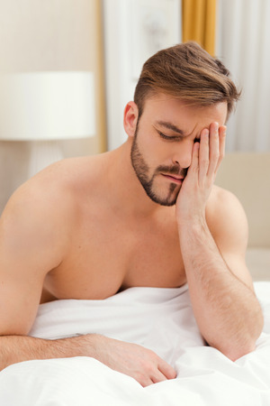 touching face: Early wake up. Depressed young man sitting in bed and touching face with hand Stock Photo