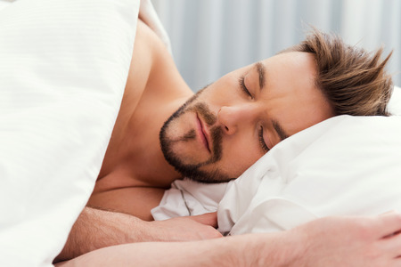 Man sleeping. Handsome young shirtless man sleeping in bed